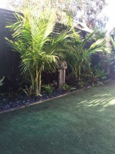 Balinese style garden with palms and Buddha statue