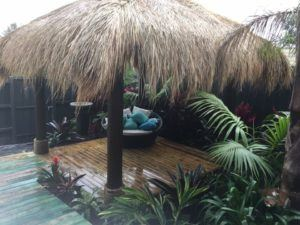 Bali thatched hut with polished timber floors and surrounded by garden